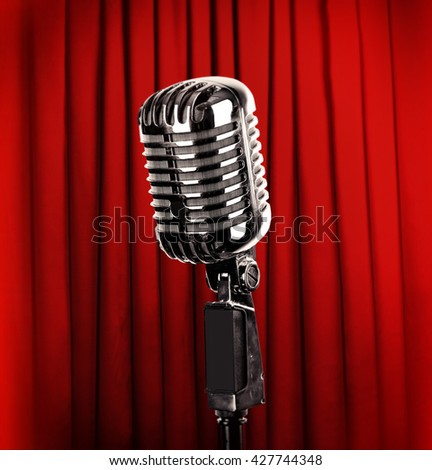 Retro silver microphone on red curtain background