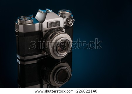 Retro slr camera on dark blue background - stock photo