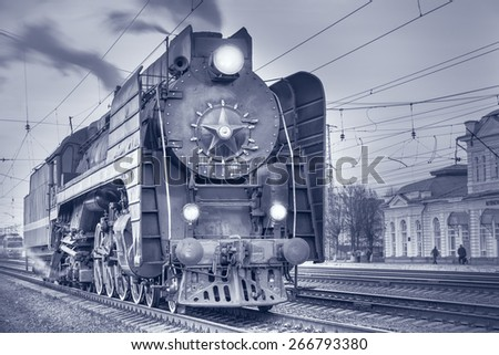 Retro steam locomotive stands on the station at evening time. - stock photo