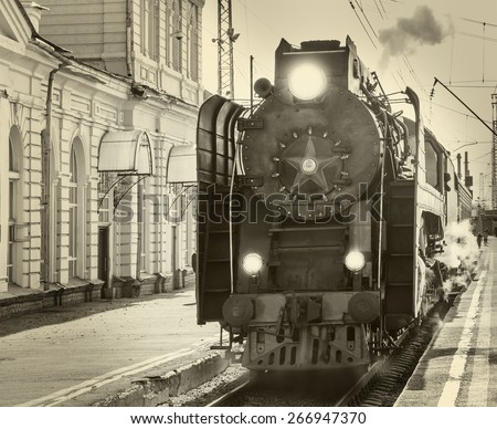 Retro steam train arrives to the station. Vintage image. - stock photo