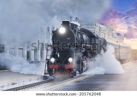 Retro steam train departs from the railway station at sunset. - stock photo