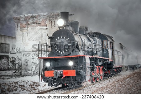 Retro steam train goes fast on the abandoned buildings background. - stock photo