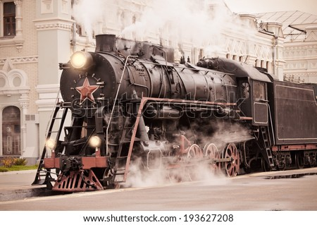 Retro steam train stands on the railway station. - stock photo