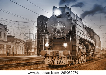 Retro steam train stands on the station at evening time. Vintage image. - stock photo