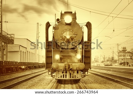 Retro steam train stands on the station at sunset time. Vintage image. - stock photo