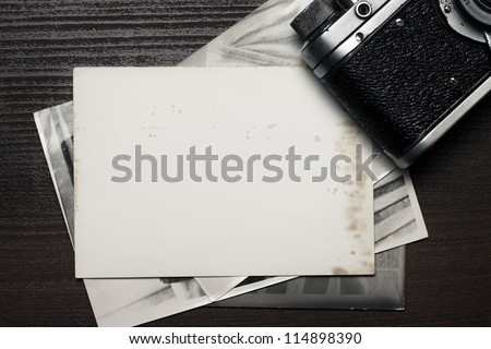 retro still camera and some old photos on wooden table - stock photo