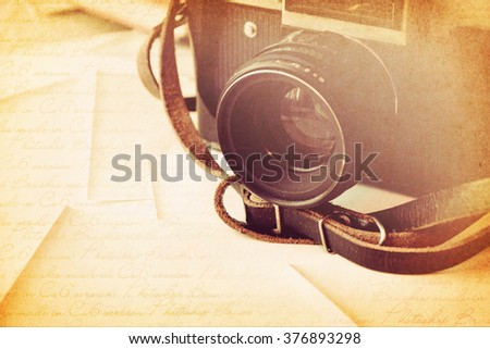 Retro still camera and some old photos on wooden table. - stock photo