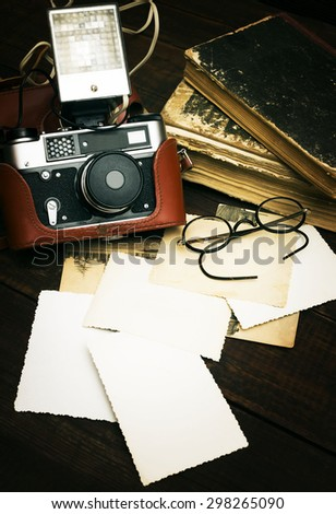 retro still camera and some old photos on wooden table background - stock photo