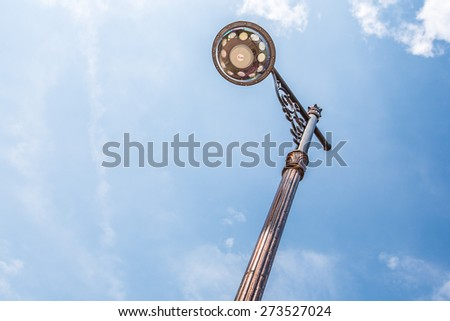 Retro street lamp against cloudy sky - stock photo