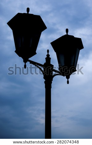 Retro street lamp shining at night against cloudy sky - stock photo