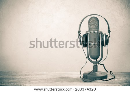 Retro studio ribbon microphone from 50s with headphones on table. Vintage old style sepia photo - stock photo