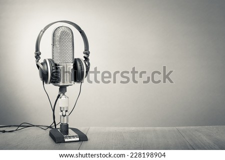 Retro studio ribbon microphone with headphones on table. Vintage old style greyscale photo