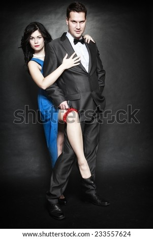 Retro style attractive couple in love, rich gangster and charming woman with gun on black background - stock photo