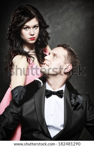 Retro style attractive fashionable couple in love, rich gangster with charming woman on black background - stock photo