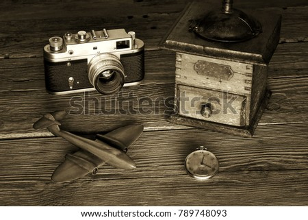 Retro style camera, grinder, watch and a toy plane on a wooden background