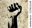 Retro style clenched fist held high in protest against grunge concrete wall background indicating revolution or aggression. - stock photo
