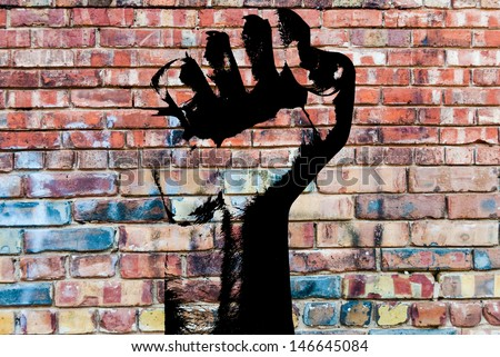 Retro style clenched fist held high in protest against grunge concrete wall background indicating revolution or aggression. Graffiti fist. - stock photo