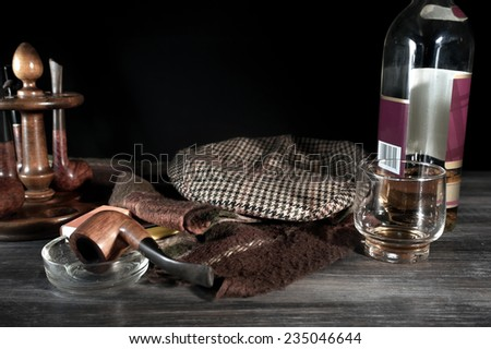 Retro style composition. Vintage items such as old hat, scarf, tobacco pipes, glass, and bottle of whiskey on table