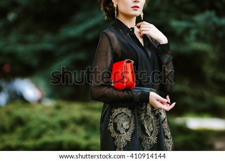 Retro style. Elegant glamor lady with clutches. Fashionable woman with a red bag in her hands and black evening dress. - stock photo