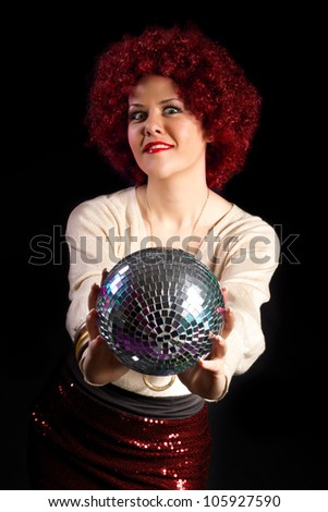 Retro style female disco dancer holding a shiny disco ball - stock photo