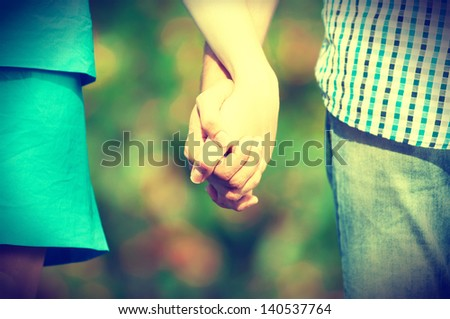 Retro style grunge shot of friendship and love of man and woman: two hands over green nature park? - stock photo