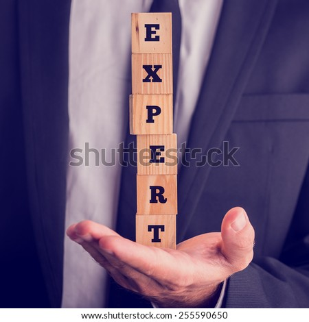 Retro style image of a businessman holding a stack of six wooden cubes with the letters EXPERT balanced on his palm. - stock photo