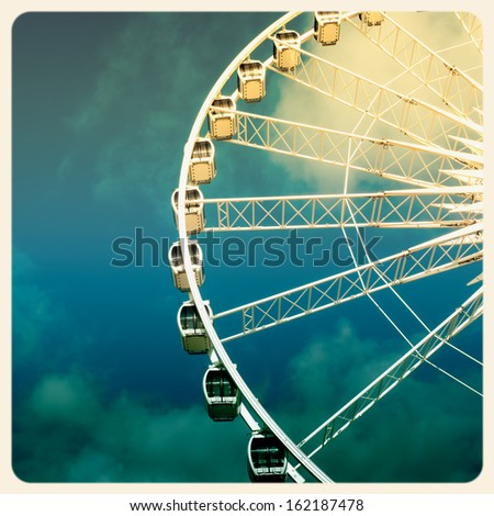 Retro style image of a ferris wheel against blue sky. Cross-processed, old instant photo effect. - stock photo