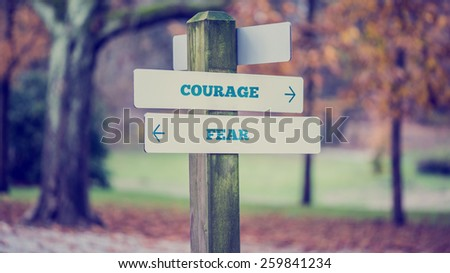 Retro style image of a rustic wooden sign in an autumn park with the words Courage - Fear offering a choice of reaction and attitude with arrows pointing in opposite directions in a conceptual image. - stock photo