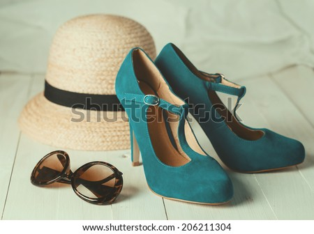 Retro style image of female fashion: straw hat, sun glasses and turquoise shoes over white wooden background. Selective focus, shallow DoF, vintage filters - stock photo
