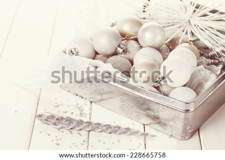 Retro style image of  silver Christmas ornaments in a silver box over white wooden background. Selective focus, shallow DoF, vintage filters - stock photo