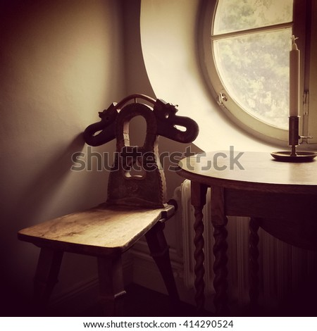 Retro style interior. Old furniture in a room with round window.