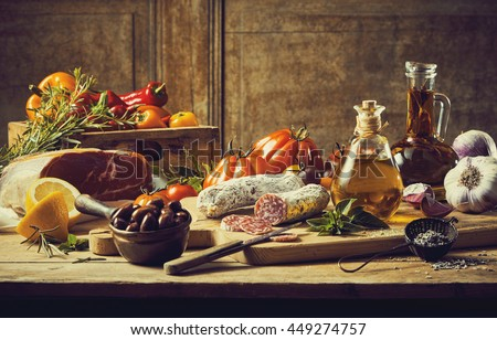 Retro style kitchen still life with fresh vegetable ingredients, cuts of cold meat and salami, condiments and olive oil on a rustic wooden table