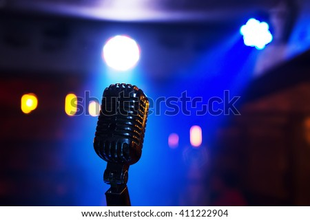 Retro style microphone on stage in the spotlight performance of the musical group. Microphone for rock, rock'n'roll and rockabilly music. Microphone in blue light og stage. - stock photo