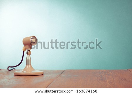 Retro style microphone on table front  mint green wall background - stock photo