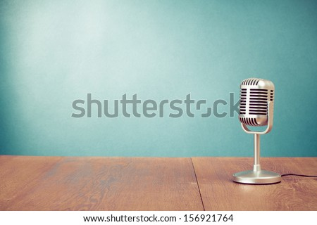 Retro style microphone on table in front aquamarine wall background - stock photo