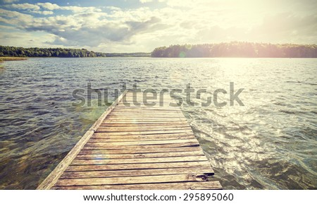 Retro style old wooden pier with flare effect at sunset. - stock photo