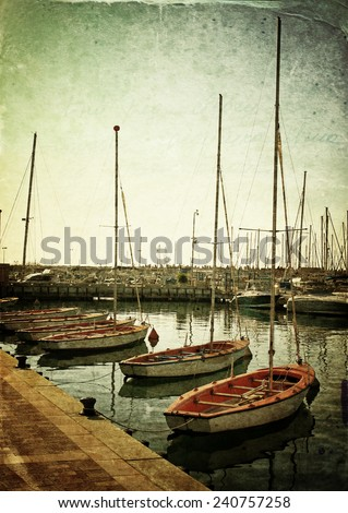 retro style photo of boats in the marina, image is textured with overlay - stock photo