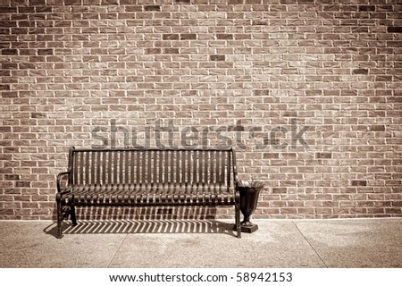 Retro style photo of metal bench against a brick wall - stock photo