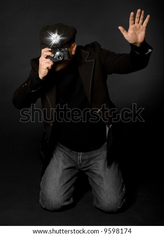 Retro style photographer with vintage camera and flash holding up his hand taking a picture - stock photo