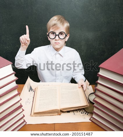 Retro style portrait of a boy with an old book raising the index finger up
