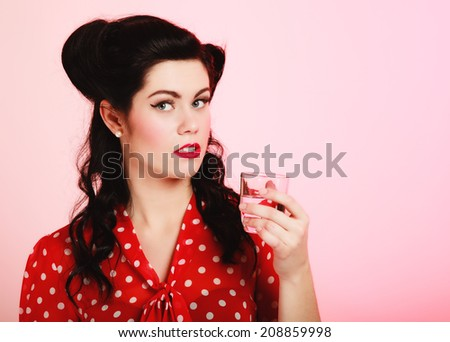 Retro style. Portrait of stylish young woman brunette pinup girl drinking water drink beverage from glass on pink. - stock photo