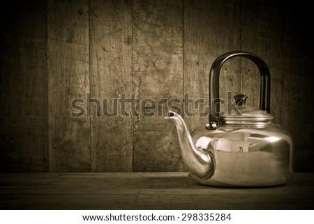 Retro style still life of old aluminium kettle - stock photo