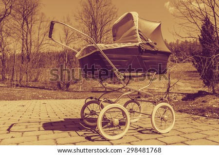 Retro style stroller baby carriage outdoors in nature on sunny day with old faded sepia filter - stock photo