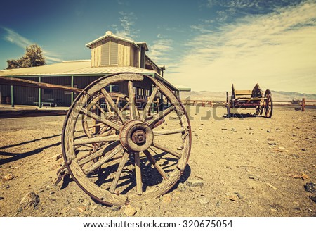 Retro style Western postcard with old carriages and saloon, Death Valley, USA. - stock photo