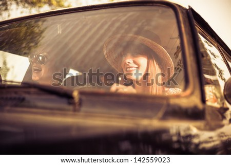 Retro style woman driving old timer car. Traveling with her friends.