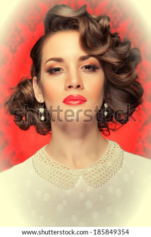 Retro style woman toned image on red vintage background. Professional make up and hairstyle. Studio lighting - stock photo