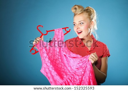 Retro style. Young happy woman shopping for dress, shopper girl choosing pink dress during sale.