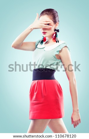 Retro style young woman closed her face with one hand but looking at the camera between her fingers. She's wearing big fancy earrings, blue background - stock photo
