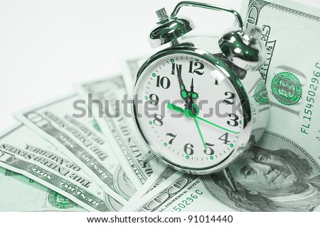 Retro styled alarm clock covered pile of money isolated on white. Time is money concept - stock photo