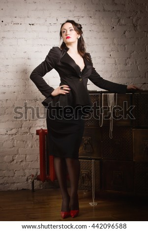 Retro styled fashion portrait of a woman dressed black suit